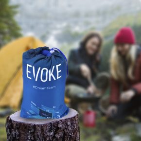 Female friends cooking with skillet over kerosene camping stove at remote campsite